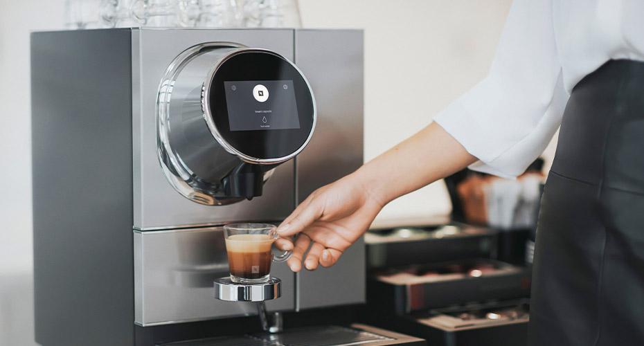 kobieta podnosi filizanke kawy nespresso